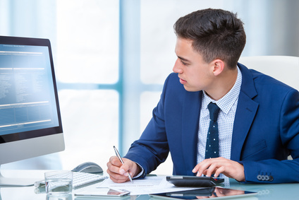 Close up portrait of young accountant doing on line internet transaction. Young man comparing documents on computer screen.