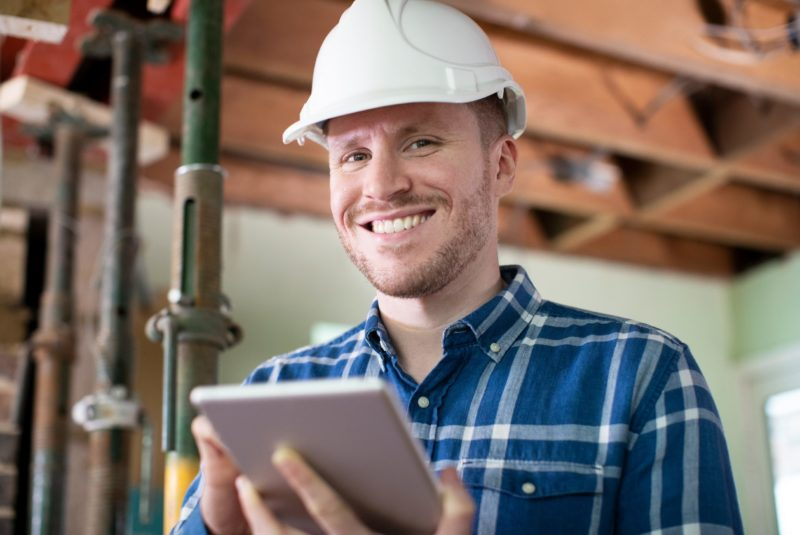 Portrait Of Architect Inside House Being Renovated Using Digital Tablet